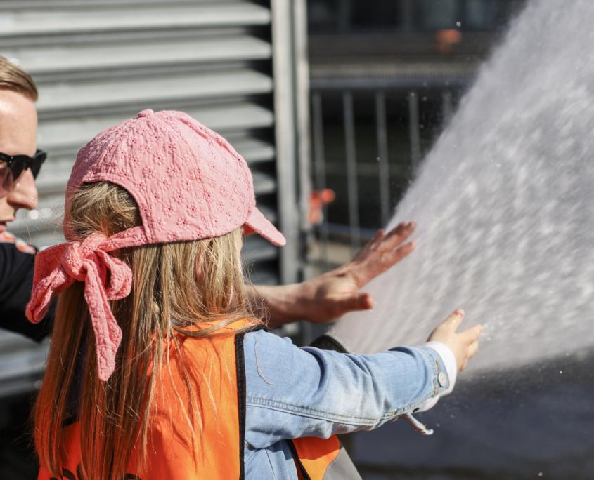 Et barn spyler med brannslange på arrangementet åpen brannstasjon
